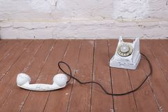 White vintage phone with the picked-up on a wood and white wall background. White vintage phone with the picked-up on a brown wood and white wall background royalty free stock images
