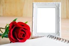 White vintage photo frame and red rose with open diary. Royalty Free Stock Photo