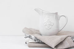 White vintage pitcher on a stack of linen towels, styled image with copyspace for product marketing. Social media, banner, header template Royalty Free Stock Images