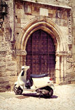 White vintage scooter near medieval gate Royalty Free Stock Image