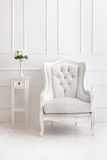 White vintage style armchair and vase of flowers on desk Royalty Free Stock Photo