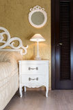 White vintage style nightstand. With a lamp in a bedroom Royalty Free Stock Images