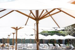 White vintage umbrella at the pool side. With the comfortable bed cushion in the hotel resort Stock Image