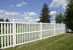 White vinyl fence by green lawn Royalty Free Stock Images