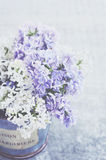 White and violet lilac flowers in vintage vase on grey background Stock Photos