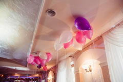 White, violet and pink balloons hang under the ceiling.  stock image