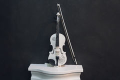 White violin on a pedestal on a black background Royalty Free Stock Photography