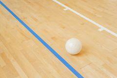 White volleyball on the floor in the gym.  stock image