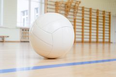 White volleyball on the ground in the school gym.  stock photo