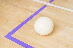 White volleyball on the ground in the school gym . White volleyball on the ground in the school gym stock photo