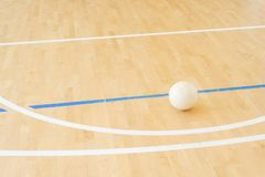 White volleyball on the ground in the school gym.  royalty free stock image