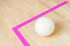 White volleyball on the ground in the school gym.  stock photos