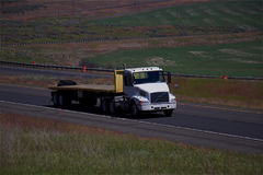 White Volvo Semi-Truck / Empty Flatbed Trailer Royalty Free Stock Photography