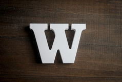White W letter on dark wooden background Royalty Free Stock Images