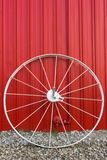 White Wagon Wheel. Large white wagon wheel against a red barn wall Stock Photography