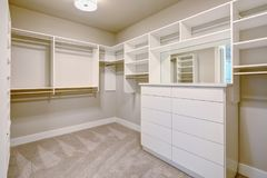 White walk-in closet with shelves, drawers and clothes rails royalty free stock photos