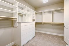White walk-in closet with shelves, drawers and clothes rails stock photos