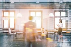 White wall bar with wooden benches toned. African American man and a businesswoman in a white wall cafe interior with a concrete floor, wooden tables and benches Royalty Free Stock Photo