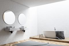 White tub in a white bathroom corner. White wall bathroom corner with a white tub, a double sink and two round mirrors. 3d rendering mock up Royalty Free Stock Photo