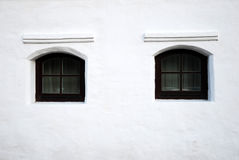 Wall design. Two symmetry decorative black windows of a white building Royalty Free Stock Images