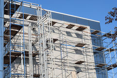 White wall building scaffolding. Metal structures on the white wall of the new building Royalty Free Stock Images