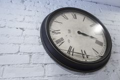 White brick painted wall waith colock Losing time, broken minute hand. White wall clock with broken minute time hand lose of time, broken time, losing time Royalty Free Stock Photo