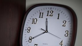 White wall clock. Oval wall clock shows 11:40. Time royalty free stock image