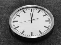 White wall clock with silver edge on gray background. royalty free stock photography