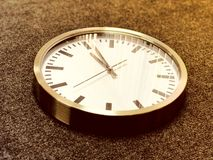 White wall clock with silver edge on gray background. stock photos