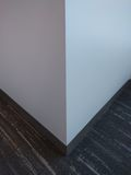 White wall corner. A white wall corner over grey carpet. Natural lighting Royalty Free Stock Images