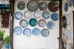 White wall decorated with many ceramic plates. In blue and turquoise tones with plants in pots on left side and iron tray hangin on wall on right side Stock Photos