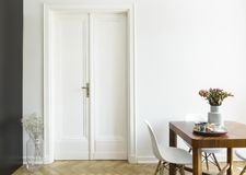 A white wall with double door next to a wooden breakfast table and chairs in a dining room interior. Real photo. Concept stock photos
