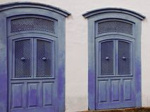 White wall facade with two blue wooden doors stock images