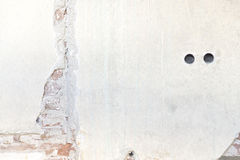 White wall with holes and crack where you can see the bricks Royalty Free Stock Photography