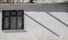 White wall of the house, a window on the wall, two parallel shadows create a rhythm in the photo,. The sun`s backlight creates an effect of the peace of the Stock Image