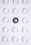 White wall with identical round white not numeral clocks and one unique dark clock. Time concept background.  Royalty Free Stock Photography