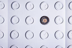 White wall with identical round white not numeral clocks and one unique dark clock. Time concept background.  Royalty Free Stock Images
