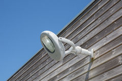 White Wall lamp on the wooden house outside under blue sky Royalty Free Stock Photography