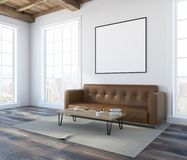 White wall living room corner, brown sofa, poster. White wall living room interior with a soft brown sofa, a coffee table and a framed poster on the wall. A side Royalty Free Stock Photography