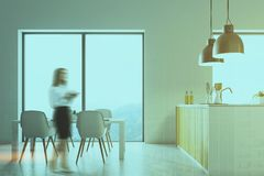 White kitchen, wooden countertops blur. White wall loft kitchen interior with a concrete floor, and white countertops under original lamps. A table with white Stock Photos