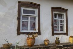 White wall of  old clay house with two windows with wooden frame. S. Crafted national curtains on the windows. Handmade crokery along the wall. Ancient Ukrainian Royalty Free Stock Photos