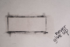 White wall with painted frame and nevergive up writen on it, Royalty Free Stock Photos