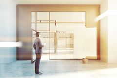 White wall poster gallery, glass door, businessman. Poster gallery with beige and white walls, a concrete floor and glass doors. A vertical mock up poster in the Royalty Free Stock Images