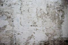White wall texture with peeling paint and slime marks. Old wall with white paint peeling off texture in black and white tone royalty free stock photo