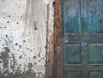 The white wall of a village house with spots of mud and a vintage green door, worn from a long use, left an empty place for text o Royalty Free Stock Image