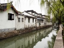 White walled houses reflected in canal waters in historic downtown Suzhou. Water canal in Suzhou old town lined with white walled houses Royalty Free Stock Photo