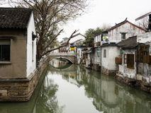 White walled houses reflected in canal waters in historic downtown Suzhou. Water canal in Suzhou old town lined with white walled houses Stock Photo