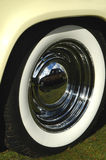 White walled tire. Reflection off the chrome of a white walled vintage car wheel Stock Images