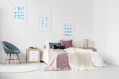 King size bed in bedroom. White walls bedroom interior with posters, grey armchair, bedside cabinet and a king size bed stock photography