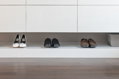 White wardrobe with male and female shoes. On shelve Stock Photography